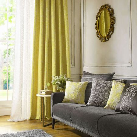 Kai -  Althea Fabric Collection - Grey sofa with white voile and lime green floor-length curtains, grey and lime green cushions, all with lace effect, and oval framed mirror