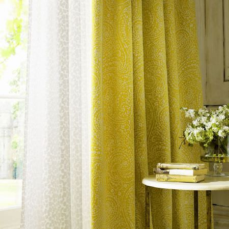 Kai -  Althea Fabric Collection - White semi-transparent curtains with a barely visible pattern, behind lime green curtains with a subtle paisley print, with a round table