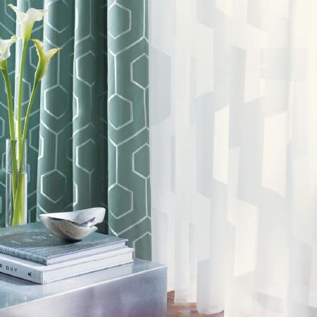 Kai -  Casson Fabric Collection - Two types of curtain patterned with basic geometric shapes in green silver and white next to a metal table