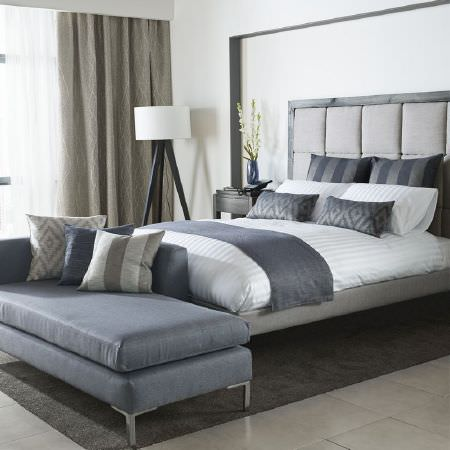 Kai -  Couture Fabric Collection - White bedding on a grey bed with dark grey cushions and a throw, a dark grey chaise longue and a black and white floor lamp