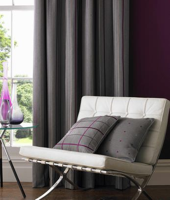 Kai -  Fabian Fabric Collection - White chair seating pads with a spotted and a tartan grey pillow and a grey striped full-length curtain providing a modern touch