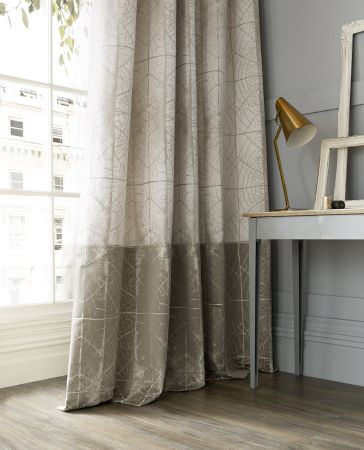 Kai -  Genoa Fabric Collection - A pale blue table with a cream top, white frames, a gold lamp, and subtly patterned white curtains with a light grey base