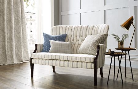 Kai -  Genoa Fabric Collection - A white and grey striped sofa with dark wood legs, 3 patterned cushions, white-grey curtains, two round tables, and a lamp