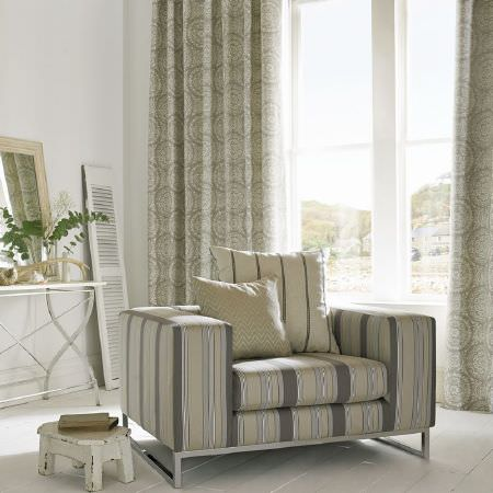 Kai -  Lamorna Fabric Collection - Wide cream, white and grey striped armchair with scatter cushions, patterned cream curtains, a white side table and a small white stool