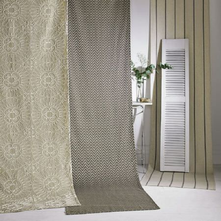 Kai -  Lamorna Fabric Collection - Cream and grey striped fabric with a white shutter, next to grey and cream zigzag fabric and cream fabric covered in white embroidery