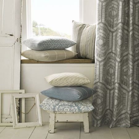 Kai -  Lamorna Fabric Collection - Striped and patterned light blue and cream cushions, with grey patterned curtains, a small rustic white wood stool, and white picture frames