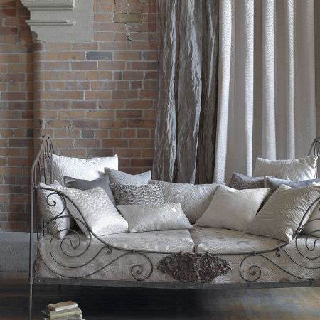 Kai -  Luminere Fabric Collection - A metal framed day bed withvarious white, silver and grey seat and scatter cushions, plus plain white and grey curtains