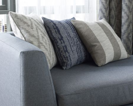 Kai -  Maderno Fabric Collection - Plain light grey upholstered sofa, white cushion with silver geometric design and interesting blue cushion