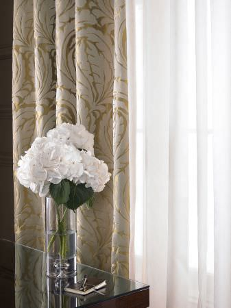 Kai -  Maurelle Fabric Collection - Corner of a room with a glass vase of flowers and gold and white curtains