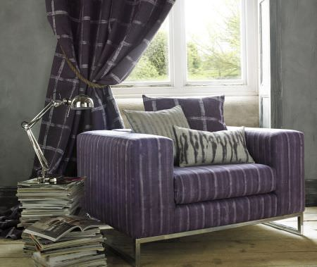 Kai -  Starla Fabric Collection - A square armchair covered with purple stripes, with purple checked curtains, purple and grey cushions, and a silver lamp