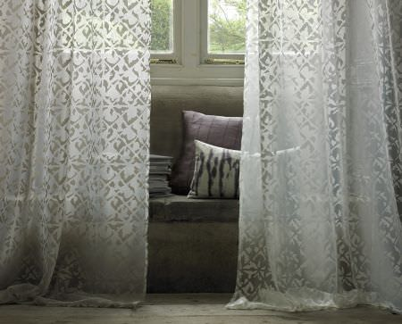 Kai -  Starla Fabric Collection - Translucent white and grey curtains with a small, subtle pattern, in front of a grey cushion and a square purple cushion