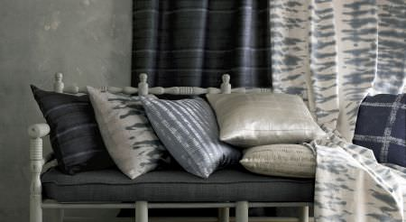 Kai -  Starla Fabric Collection - A charcoal seat cushion on a grey bench, with black, grey and silver scatter cushions, and two patterned curtains
