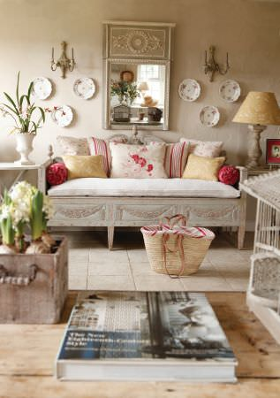 Kate Forman -  Kate Forman Fabric Collection - A country house setting with a rustic bench with a white seating pad and a set of red, white and yellow striped or flowery cushions