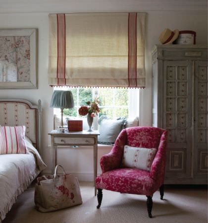 Kate Forman -  Kate Forman Fabric Collection - Country house bedroom with white and red striped bedspread and roman blinds, and a red upholstered armchair with classic floral pattern