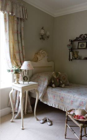 Kate Forman -  Kate Forman Fabric Collection - Bedroom setting for children showing a blue and floral striped duvet with pinched edges and a white curtain valance and curtain with roses