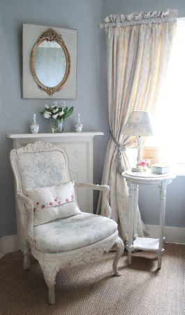 Kate Forman -  Kate Forman Fabric Collection - 18th century classic padded armchair with white fabric and a faint blue impressions of flowers, and a pinched white curtain