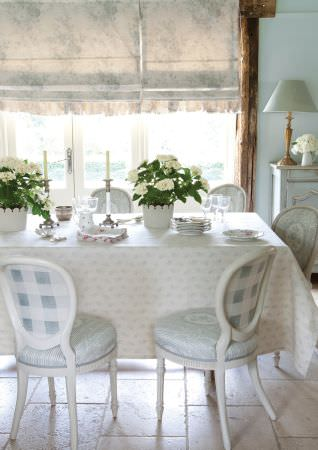Kate Forman -  Kate Forman Fabric Collection - Country style dining room with white and blue plaid and floral seats, white roman blinds with faint flower imprint and a flowery tablecloth