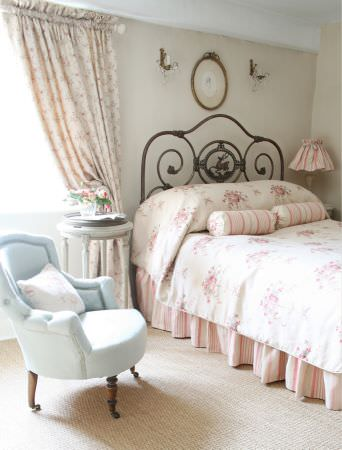 Kate Forman -  Kate Forman Fabric Collection - A bedroom showing white and red striped pillows, a white duvet cover with big flowers, a pink striped bedspread, and blue upholstered chair