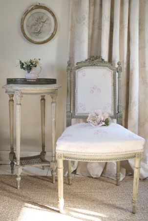 Kate Forman -  Kate Forman Fabric Collection - White padded classic chair with faint pink flowers and a cream white curtain with faint grey flower impressions