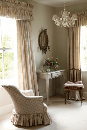 Kate Forman -  Kate Forman Fabric Collection - Creamy coloured curtain valances with red floral design and an upholstered armchair with small floral pattern in a country house setting