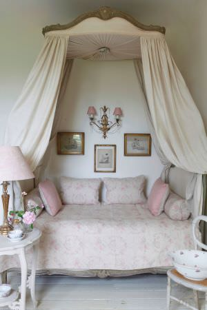 Kate Forman -  Kate Forman Fabric Collection - Antique four poster bed frame with a cream white quilt and cushions with light pink flower imprints