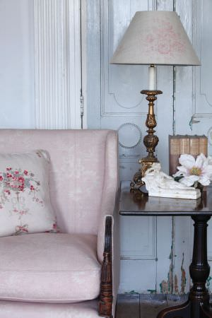 Kate Forman -  Kate Forman Fabric Collection - Antique classic pink upholstered chair with leaf impressions, a white cushion with red flowers and a light pink lamp cover