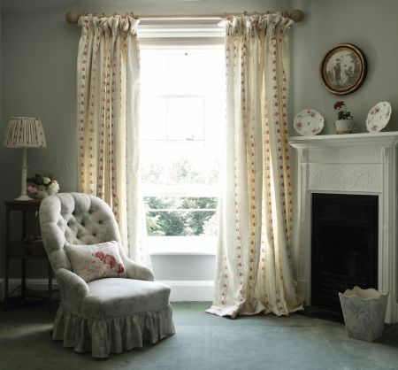 Kate Forman -  Kate Forman Fabric Collection - White double pinch curtain with red flower chains and a grey upholstered classic armchair with a white flowery pillow in a country house