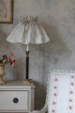 Kate Forman -  Kate Forman Fabric Collection - White lamp shade and wall paper with faint detailed flower impression and an antique chair with flower chain upholstery