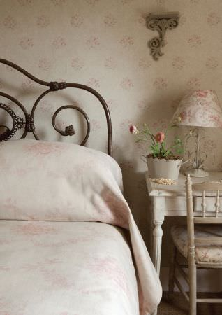 Kate Forman -  Kate Forman Fabric Collection - An antique style bedroom with a white quilt and pillows with faint rose flower impressions and fabric wall paper with pink flower pattern