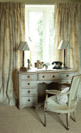 Kate Forman -  Kate Forman Fabric Collection - Rustic drawing room setting with pinched top curtains with grand floral design and an antique chair  upholstered with plain sandy fabric