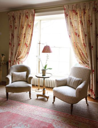 Kate Forman -  Kate Forman Fabric Collection - Classic upholstered armchairs with small flower pattern and striped pillows in front of light yellow curtains with detailed red rose design