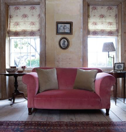 Kate Forman -  Kate Forman Fabric Collection - Summer pink upholstered couch with two plain brown cushions, and white roman blinds with flower impressions