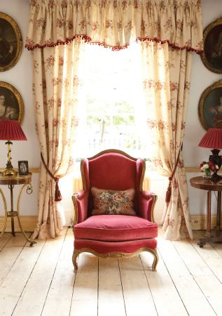 Kate Forman -  Kate Forman Fabric Collection - Light yellow curtain valance with red lining and flowers in classic design, behind an antique plain red upholstered armchair