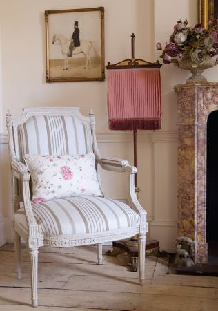 Kate Forman -  Kate Forman Fabric Collection - An antique armchair with white and light brown striped fabric padding and a white pillow with classic flower imprint