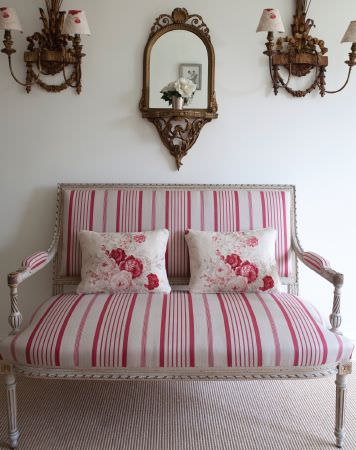 Kate Forman -  Kate Forman Fabric Collection - Red and white striped upholstery of an antique bench with two white cushions having detailed red and pink rose impressions