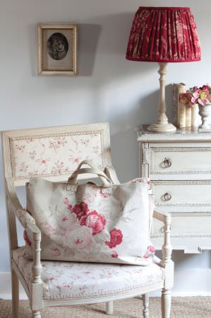Kate Forman -  Kate Forman Fabric Collection - Antique style chair with white flowery padding, a large handbag with detailed watercolour flower images and a red fabric lamp shade