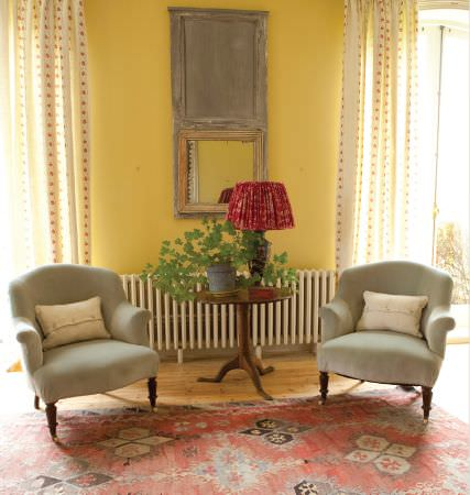 Kate Forman -  Kate Forman Fabric Collection - Classic style plain mineral blue upholstered armchairs in front of white curtains with red flower chains in a classic house setting