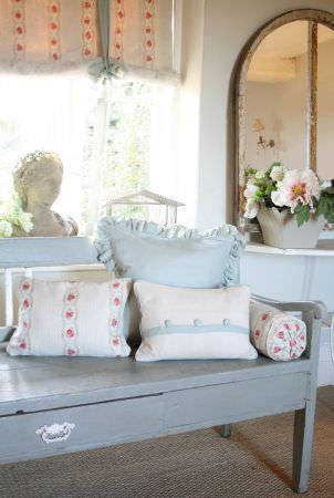 Kate Forman -  Kate Forman Fabric Collection - A rustic bench with plain blue pillows and white pillows with blue and red stripe and flower chain decorations