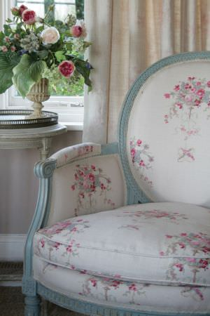 Kate Forman -  Kate Forman Fabric Collection - Classic white upholstered chair with red classic floral images and a white curtain with faded pink flower and leaf impressions