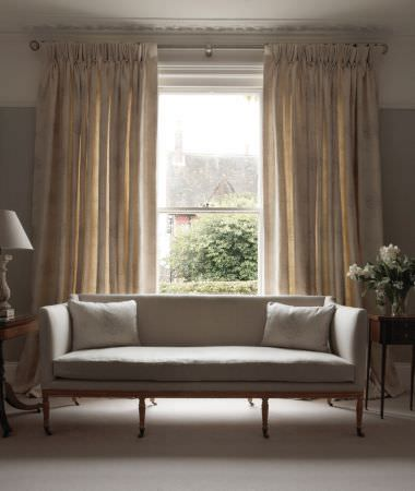 Kate Forman -  Kate Forman Fabric Collection - Pinched white curtains with faded red floral imprints, and a simple couch with cream white upholstery in a classic living room setting