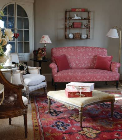 Kate Forman -  Kate Forman Fabric Collection - Red upholstered classic couch with classic floral design and plain red cushions next to a yellow upholstered footstool