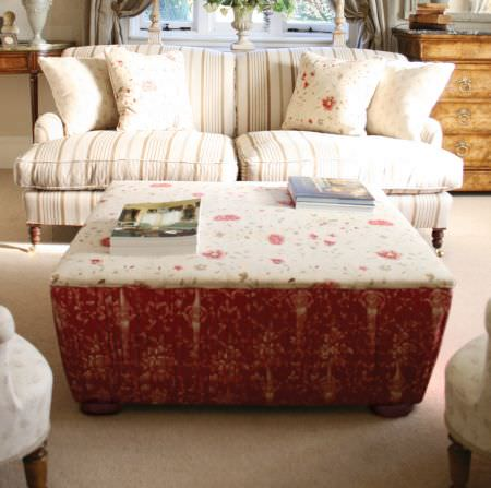 Kate Forman -  Kate Forman Fabric Collection - White and red upholstered footstool with classic floral patterns next to a white striped couch with flowery cushions