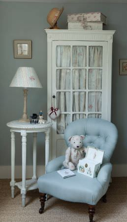 Kate Forman -  Kate Forman Fabric Collection - Light blue upholstered armchair for children, a blue, red and white lampshade and curtain in a country style child room