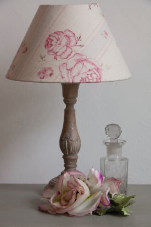 Kate Forman -  Kate Forman Fabric Collection - An antique lamp covered by a white lamp shade with light blue stripes and detailed prints of pink roses