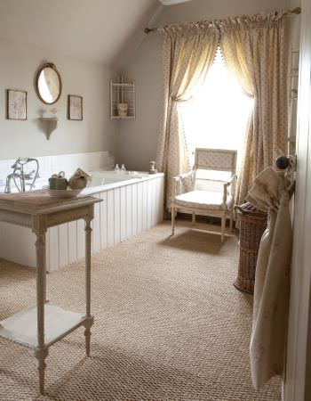 Kate Forman -  Kate Forman Fabric Collection - A bathroom with a cream coloured curtain decorated with a flower grid and an antique chair with cream coloured seating pads