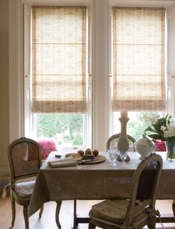 Kate Forman -  Kate Forman Fabric Collection - Sandy coloured roman blinds with red flowers and a light brown tablecloth, surrounded by wooden chairs with sandy seating pads