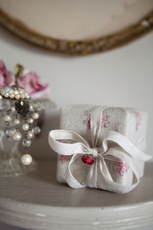 Kate Forman -  Kate Forman Fabric Collection - Present wrapped in white fabric with faded pink flowers and a white bow tie