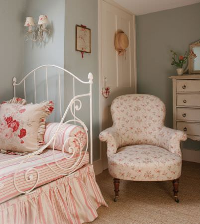 Kate Forman -  Kate Forman Fabric Collection - Antique iron bed with pink and white striped duvet, cushion, and bedding, and a white upholstered armchair with small floral impressions