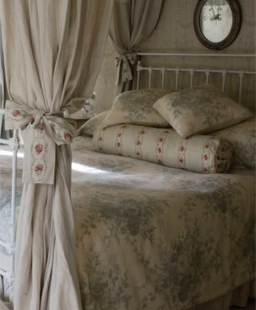 Kate Forman -  Kate Forman Fabric Collection - Rustic white quilt and pillows with classic grey/blue flower impressions, and white cushion with bands of red flower wreaths