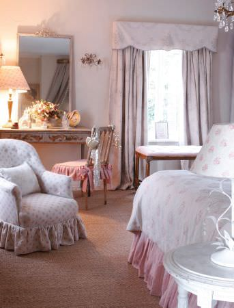 Kate Forman -  Kate Forman Fabric Collection - White duvet with pnk flower decoration and pink bedding, a classic white upholstered armchair, and a white curtain valance with blue flowers